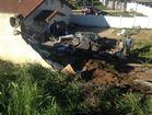 Mustang smashes through wall, down embankment
