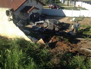 Mustang smashes through wall, down embankment