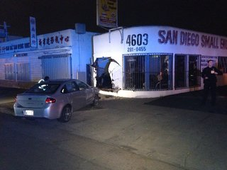 Car crashes into auto shop, 1 person extricated