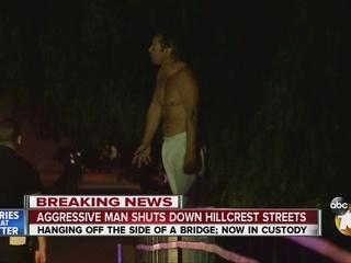 Man hangs off bridge, taunts police