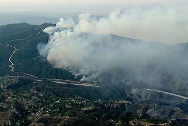 Los Angeles firefighters battle growing brush fire