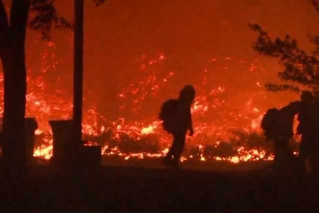 Tens of thousands flee California wildfires as hundreds of buildings burn